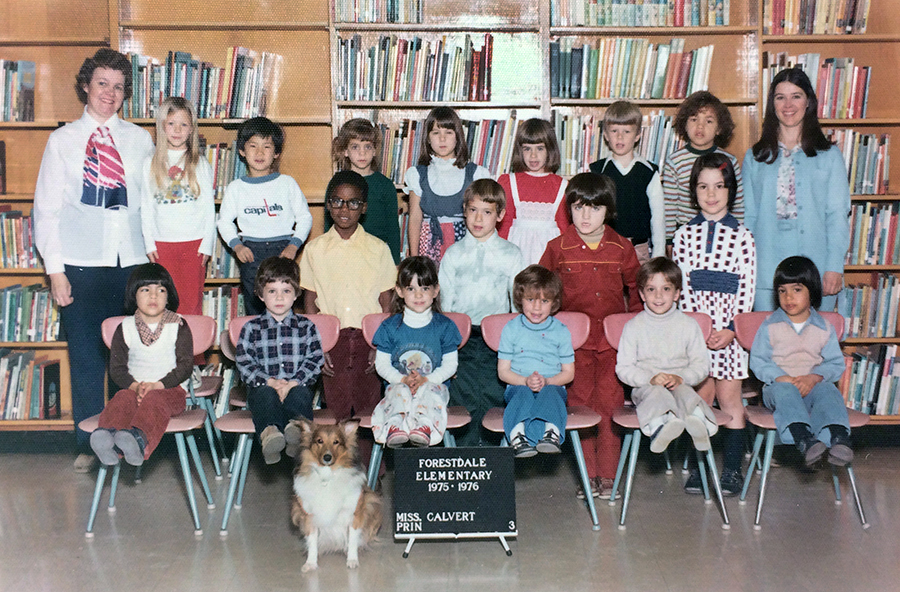 Color photograph of Mrs. Hudgins' class during the 1975 to 1976 school year. The children appear to be in first or second grade. 17 children are pictured, seven of whom are girls. Principal Calvert is standing on the left and Mrs. Hudgins is standing on the right of the children. The children are arranged in three rows with one row seated and two rows standing. In front of the seated children is a sign that reads: Forestdale Elementary, 1975 – 1976, Miss Calvert, principal. A Sheltie breed dog is sitting on the floor next to this sign.