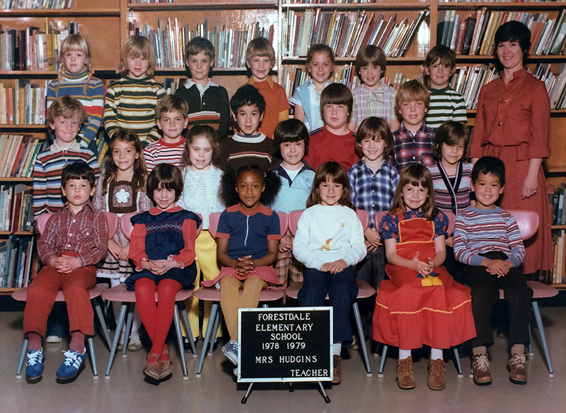 Color photograph showing Mrs. Hudgins' class at Forestdale. 23 children are pictured, arranged in four rows. Hudgins can be seen on the far right behind her students. She is wearing a red blouse and skirt.