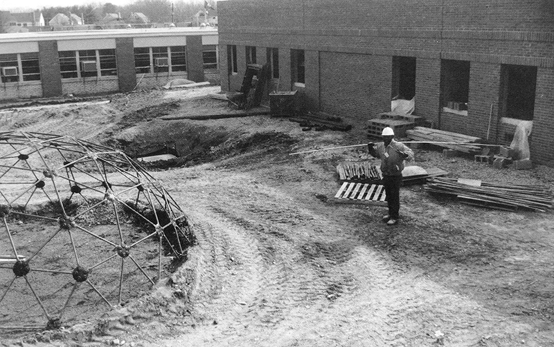 Black and white photograph of construction progress on the music room and art classroom addition to Forestdale. The picture is from our 1992 to 1993 yearbook. Window-mounted air conditioning units are visible in the classroom windows. A construction worker, wearing a hard hat, is carrying supplies on his shoulder. The new classroom wing is visible behind him. It is two-stories tall and has a brick veneer. The windows are not yet in place, and construction materials are placed around the structure.