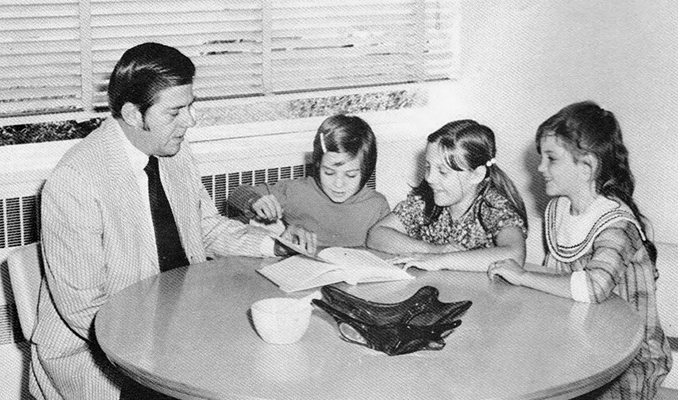 Black and white yearbook portrait of Principal Ronald West. This picture comes from a 1971 to 1972 yearbook at North Springfield Elementary School where West became principal after leaving Forestdale. He is seated at a small round table reading a book to three students.