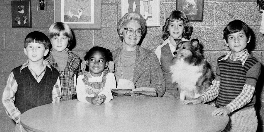 Black and white portrait of Principal Nancy Calvert from Forestdale's 1977 to 1978 yearbook. She is seated at a table surrounded by five students. Dutchess is seated on a stool between two students to the right of Calvert.