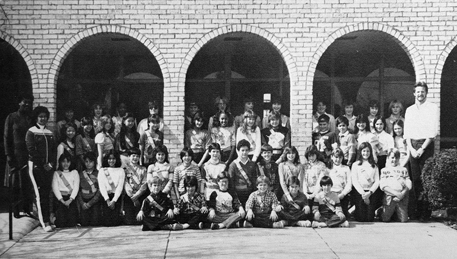 Black and white photograph from our 1983 to 1984 yearbook showing Forestdale's Safety Patrol. A large group of approximately 45 students are posed under the archways that formerly lined the main entrance to our school. The students are wearing safety patrol belts and sashes. Several adults are pictured with the group.