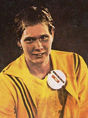 Color photograph of Olympic swimmer Melissa Belote. It is a head-and-shoulders portrait. She is wearing a yellow jacket over a yellow t-shirt.